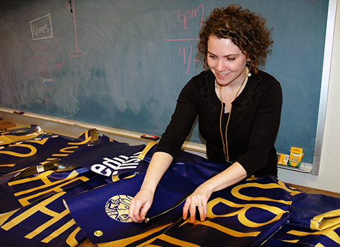 A photo of Assistant Professor on Consumer & Family Studies/Dietetics Kelly Reddy-Best adjusting a jacket made from old SF State banners.