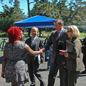 A photo of California State University Chancellor Timothy White being greeted on the SF State quad by Associated Students, Inc. President Adenike Hamilton as President Les Wong and Interim Vice President for Enrollment Management and Student Affairs look on.