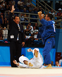 A photo of an Olympic judo athlete displaying triumphant body language following victory.