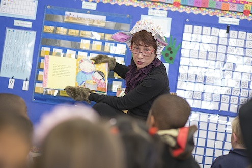 Photo of Elogeanne Grossman, executive assistant to the president, reading to students at Jose Ortega Elementary School