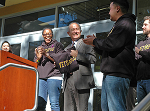 A photo of President Leslie Wong receiving a sweatshirt from the VETS@SFSU student organization during a Veterans Day ceremony at SF State.