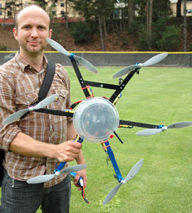 Photo of Peter Christian holding a hexagon-shaped unmanned aerial device.