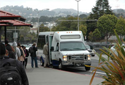 A photo of people boarding an SF State shuttle on 19th Avenue.
