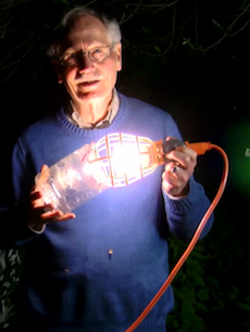Photo of Professor of Biology John Hafernik holding a zombee light trap.