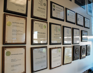 A photo of awards hanging on the wall of the Xpress newsroom.