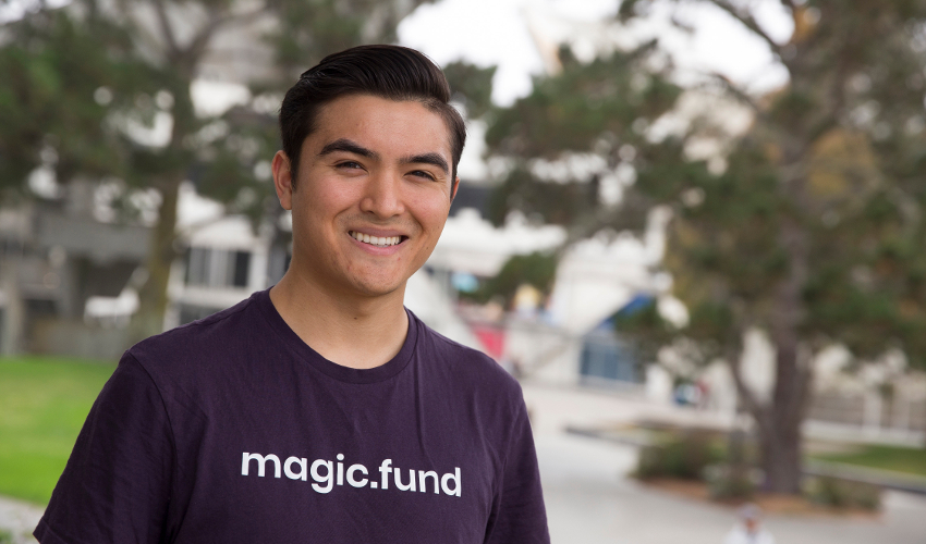 "Student Matt Greenleaf, wearing a purple shirt with the text ""magic.fund"""