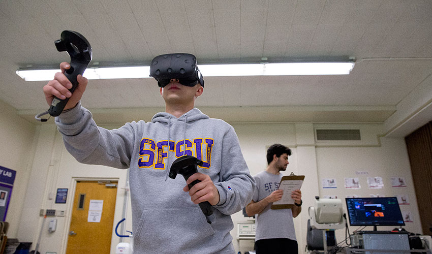 A student subject wearing a headset plays a virtual reality game in the Department of Kinesiology's exercise lab while another student holds a clipboard and watches a computer monitor.