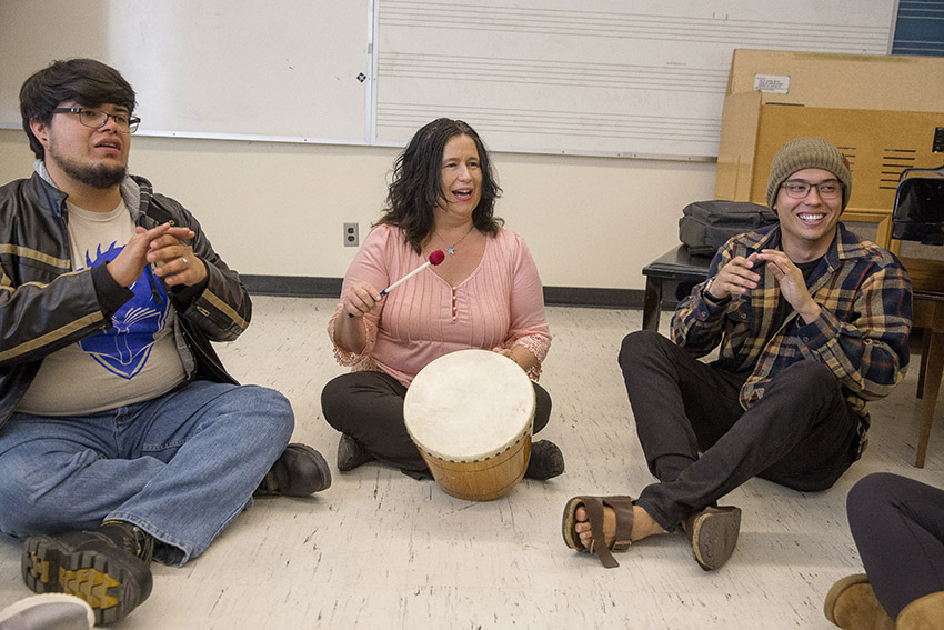 San Francisco State University Professor of Music Education Wendell Hanna sits on the floor and drums as she teaches students in her music education class.