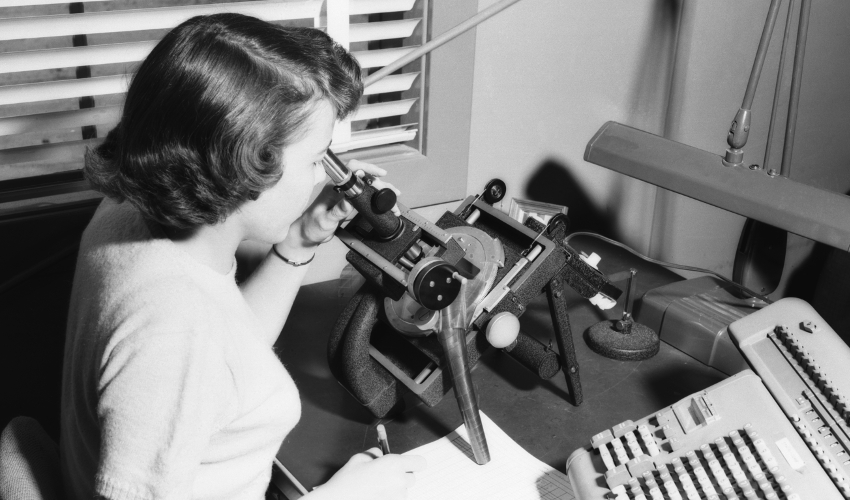 Black-and-white historical photo of woman looking into microscope