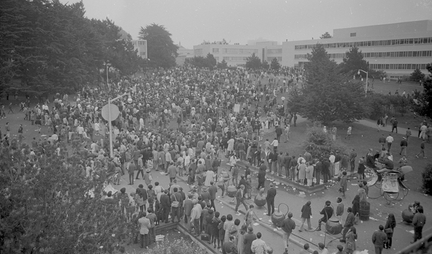 Aerial view of a crowd marching along a paved road. It appears to be a protest.